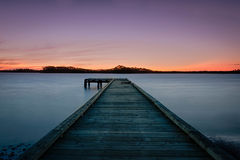 Wooden dock in lake at sunset Royalty Free Stock Image