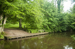 Wooden dock next to brown river. Green summer day next to the river outside of the city Stock Photos