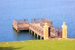 Wooden dock over blue ocean water Royalty Free Stock Photo
