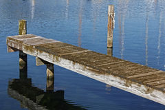 Wooden Dock. A wooden dock over calm blue water Stock Image