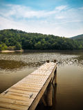 Wooden Dock Overlooking Peaceful Mountain Lake. With bold blue and gold color in the water and sky Stock Images