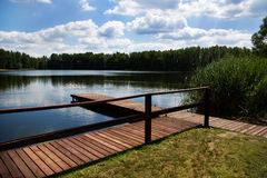 Wooden dock, pier on a lake. Empty wooden dock, pier, wharf on a lake in sunny summer day - ideal for yachting Stock Image