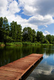 Wooden dock / pier on a lake. Empty wooden dock, pier, wharf on a lake in sunny summer day - ideal for yachting Stock Photo