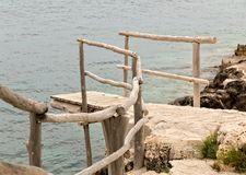 Wooden dock at a seaside cliff Stock Photos