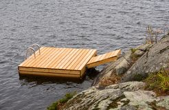 Wooden dock / swimming platform. Wooden swimming platform attached to a rocky shore Stock Photo
