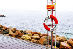 Wooden docks and life belt by the sea in Malmo in Sweden. MALMO, SWEDEN - DECEMBER 31, 2014: Wooden docks and life belt by the sea on cloudy day in Malmo, Sweden Royalty Free Stock Photos