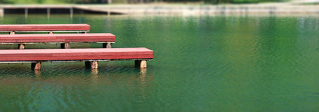 Wooden docks piers on park lake. Three red painted wooden docks piers on park lake Royalty Free Stock Images