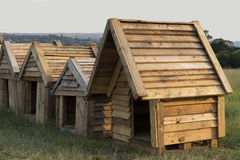 Wooden Dog Houses. Different size wooden dog kennels in a row royalty free stock photos