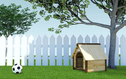 Wooden dog kennel under tree shade on green grass meadow with soccer ball and white wooden fence Royalty Free Stock Photo
