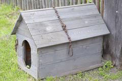 Wooden doghouse with an iron chain and a broken roof. A wooden doghouse with an iron chain and a broken roof, near a fence Royalty Free Stock Image