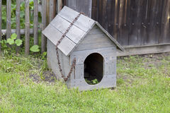 Wooden doghouse with an iron chain and a broken roof. A wooden doghouse with an iron chain and a broken roof, near a fence Royalty Free Stock Photo