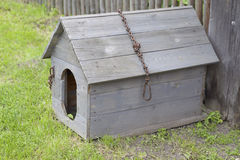 Wooden doghouse with an iron chain and a broken roof. A wooden doghouse with an iron chain and a broken roof, near a fence Stock Photos