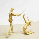 Wooden Doll in Action. Wooden Dolls in Concept of Aggression and Domination Royalty Free Stock Photo