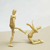 Wooden Doll in Action. Wooden Dolls in Concept of Aggression and Domination Royalty Free Stock Images