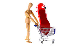 Wooden Doll buys shoes in a shopping cart. Cut out Royalty Free Stock Images