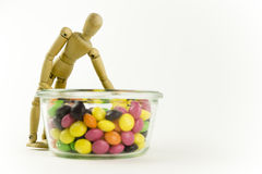 Wooden doll with candies. Happy wooden doll with a jar of candies Stock Photography