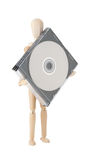 Wooden doll with CD or DVD Royalty Free Stock Photo