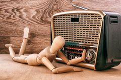 Wooden doll enjoy listening to music while lying near the radio receiver. Wooden background. Wooden doll enjoy listening to music while lying near the radio Royalty Free Stock Photography