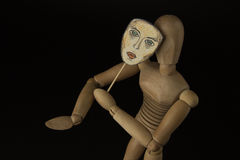 Wooden doll on hinges holds a mask in hands and covers her face Royalty Free Stock Photography