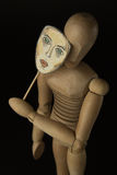 Wooden doll on hinges holds a mask in hands and covers her face Stock Photos