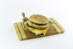 Wooden doll holding a hamburger. Wooden doll standing on a chopping board against a white background, holding a hamburger Stock Photos