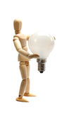 Wooden doll holding a light bulb Royalty Free Stock Photos