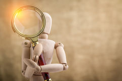 Wooden doll with magnifying glass Royalty Free Stock Photos