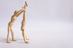 A wooden doll man exercises with his friend Royalty Free Stock Images