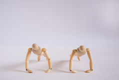 A wooden doll man exercises with his friend Stock Images