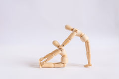 A wooden doll man exercises with his friend Royalty Free Stock Photo
