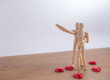 A wooden doll man on valentine day on the wooden floor with the act of love and relation. Stock Image