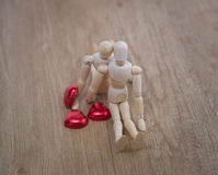 A wooden doll man on valentine day on the wooden floor with the act of love and relation. Royalty Free Stock Photos