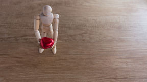 A wooden doll man on valentine day on the wooden floor with the act of love and relation. Royalty Free Stock Images