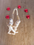 A wooden doll man on valentine day on the wooden floor with the act of love and relation. Royalty Free Stock Image