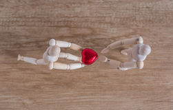 A wooden doll man in a valentine theme show his love to his couple Stock Image