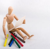 A wooden doll with a piece of paper and coloured pens Royalty Free Stock Image