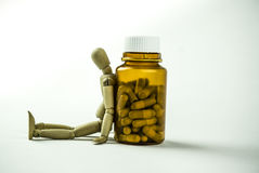 Wooden doll and pills. Wooden doll sitting next to a bottle of pills Royalty Free Stock Photography
