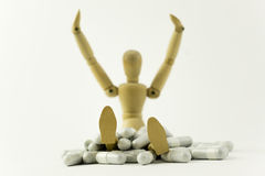 Wooden doll and pills. Wooden doll sitting in a pile of pills Royalty Free Stock Photography