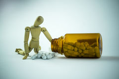 Wooden doll and pills. Wooden doll taking a pill out of a bottle Royalty Free Stock Images
