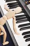 Wooden doll playing piano Stock Photography