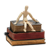 Wooden doll sit on old books Royalty Free Stock Images