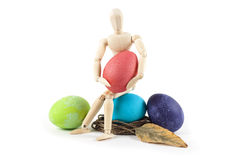 Wooden doll sitting near Easter eggs on a white background Stock Image