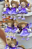 Wooden Doll Souvenirs Summer Time. Gift shop on the island Mali Lošinj, Croatia, Europe. July 2018. Wooden doll in purple dresses with a hat on the head Royalty Free Stock Images