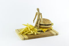 Wooden doll standing on a hamburger. Looking at some french fries Stock Images