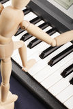 Wooden doll stepping on piano Royalty Free Stock Photos