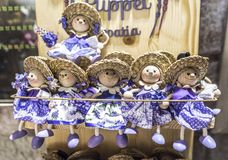 Wooden dolls dressed in purple outfits. Stock Photos