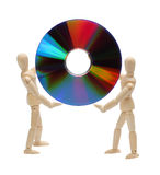 Wooden dolls holding a cd Stock Photography