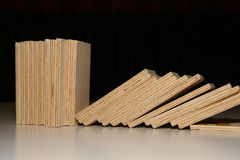 Wooden Domino. Fallen wooden domino blocks on black background stock image