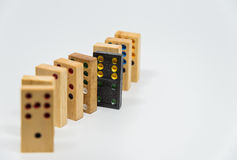 Wooden dominoes sequence with black plastic domino on white background with selective focus Royalty Free Stock Image