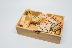 Wooden dominos in wooden box on white background with selective focus Royalty Free Stock Image